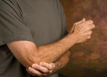 closeup of man massaging elbow